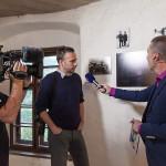 Svatopluk Klesnil při rozhovoru s moderátorem ČT před jeho fotografiemi